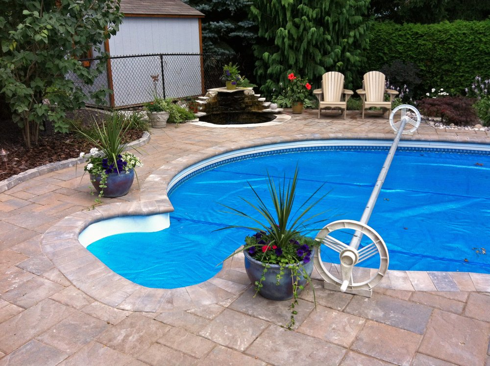 Old concrete pool deck upgraded with decorative interlock stones and peaceful waterfall beside the sitting area