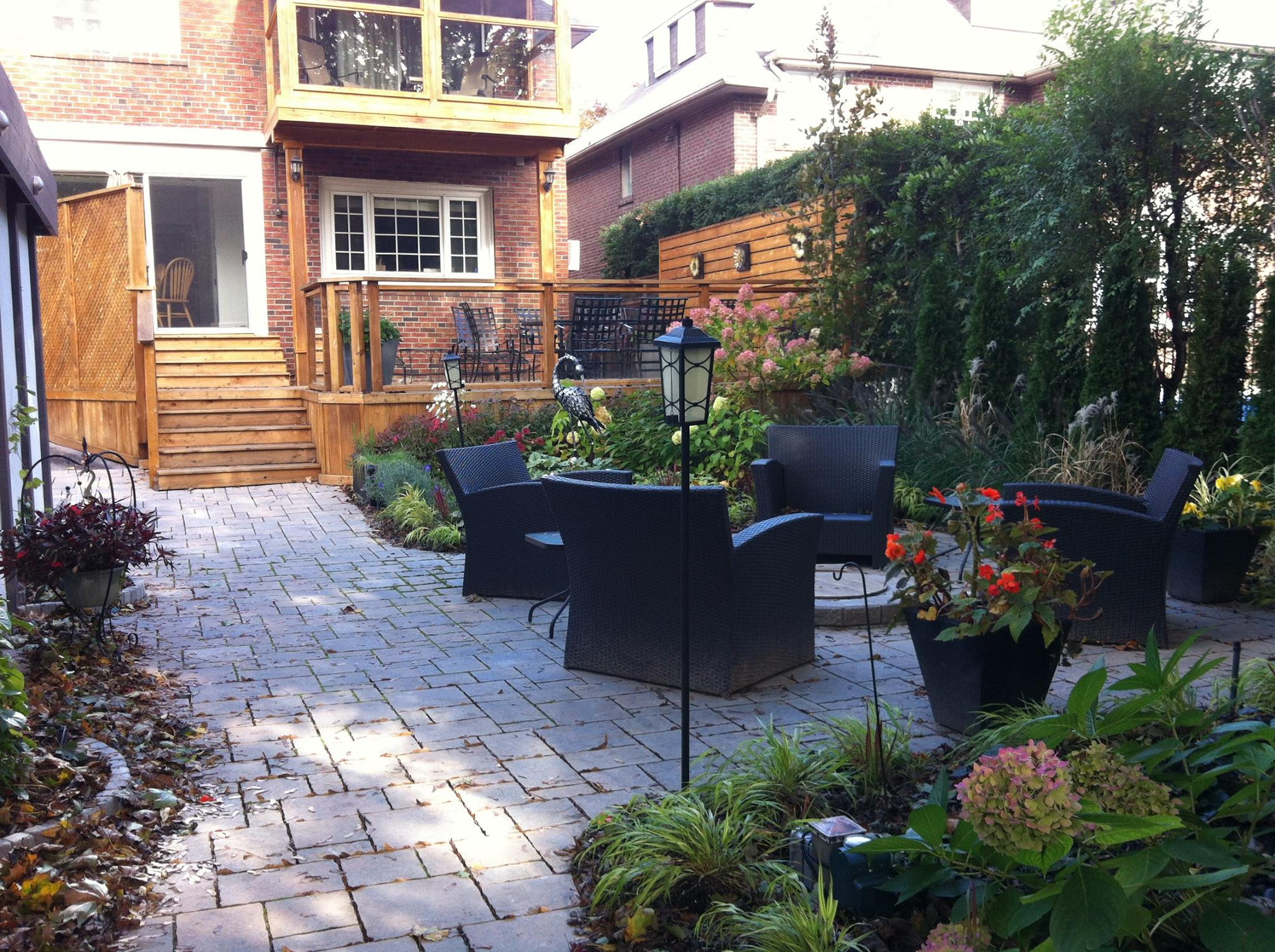 Cozy backyard patio with gas fire pit, water feature, and cedar deck with glass panel railings
