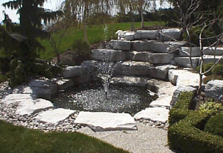 Larger waterfall and pond with fountain nozzle created using white cubicle rockery.