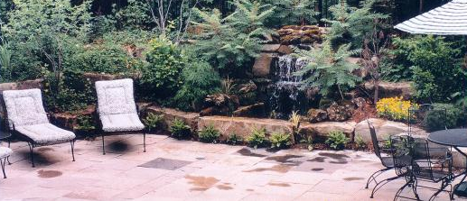 Natural flagstone, mossy rocks perennials, and dwarf Sumac truly add to the rustic character of this patio-side water feature.