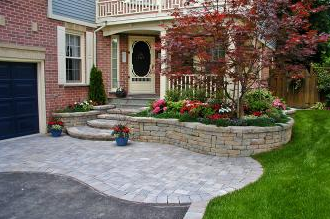 Interlock set within the asphalt driveway compliments the planter and stair design.