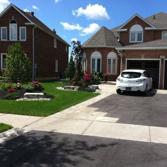 New asphalt driveway with geometric interlock accent patterns, natural stone walkway steps, landscape lighting, and full garden planting