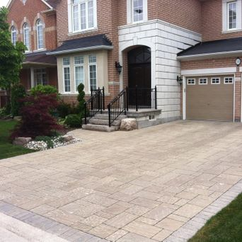 Interlock driveway, natural stone steps, flagstone on top of existing concrete porch, landscape lighting, irrigation system, and new gardens